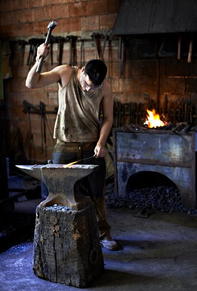 Herrero trabajando en la forja